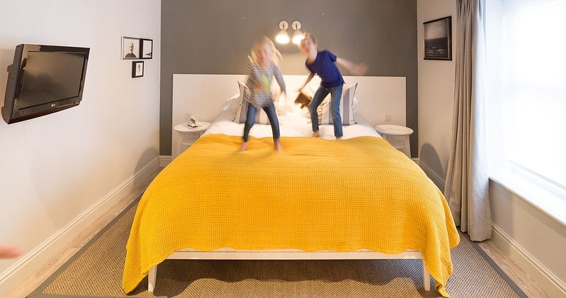 Kids jumping on the bed in the room at Watergate Bay, Newquay.
