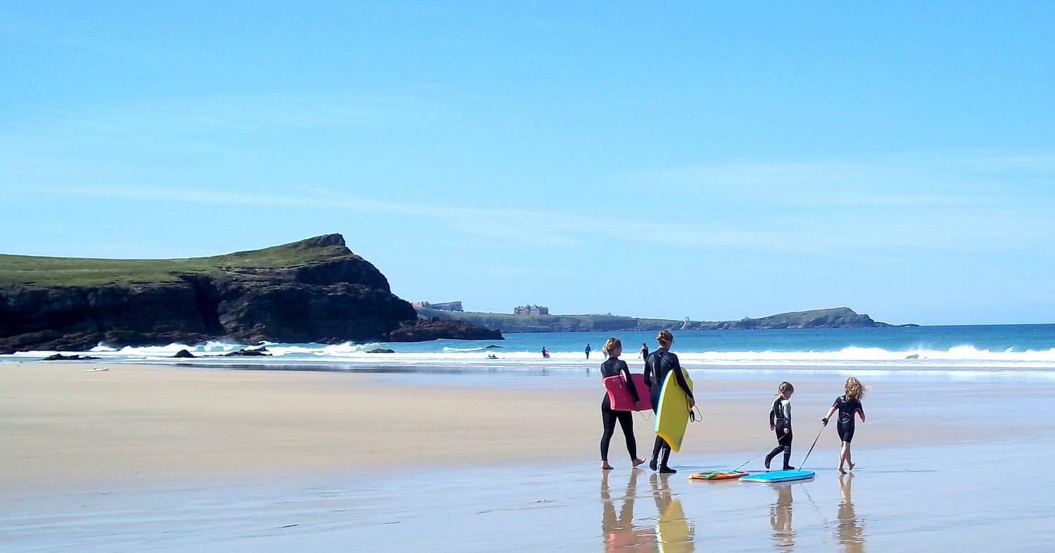 Family walking along the beach in Newquay with paddle boards.