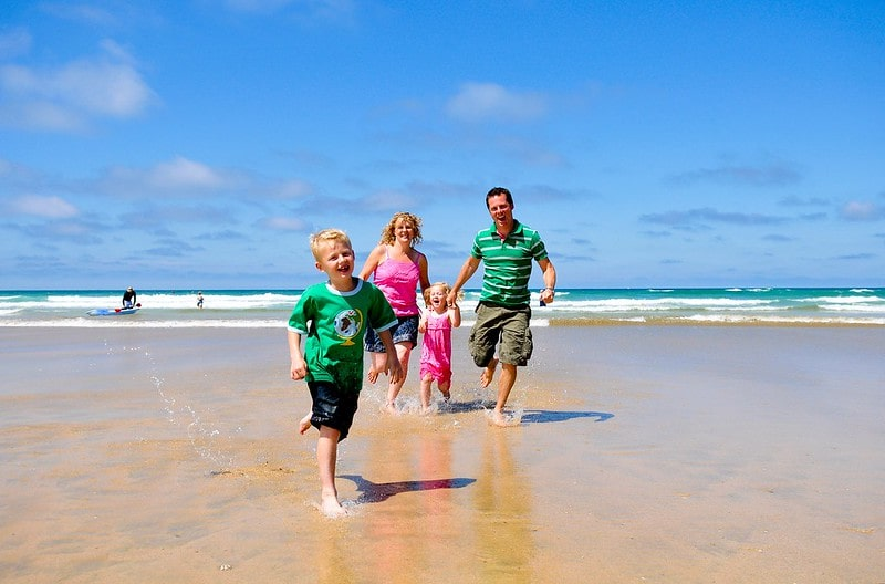 Mum and dad happily running along the beach in Newquay with their two kids.