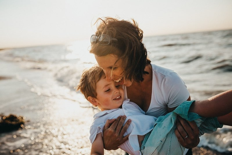 Mum carrying her son on the beach, both laughing and happy.
