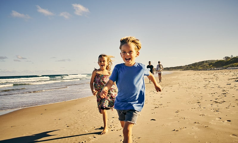 Kids happily running along the beach in Dorset enjoying the perfect family staycation.