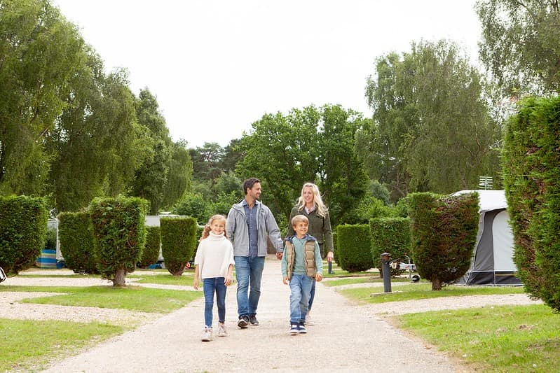 Family smiling and excited as they arrive at Sandford Holiday Park, Dorset.