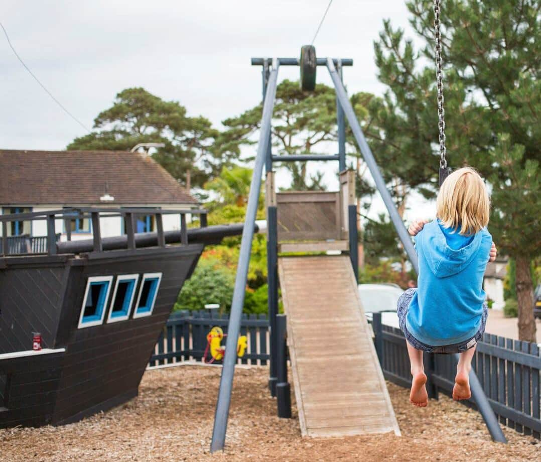 Kid having fun on the zip-line in the playground at Knoll House, Dorset.