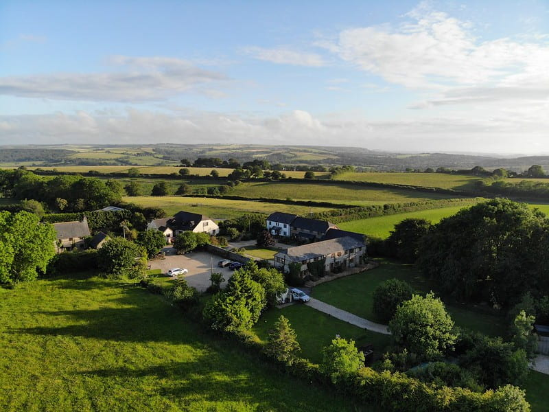Aerial view of Lancombe Country Cottages, Dorset, surrounded by rolling fields.