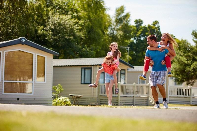 Family having a piggyback race outside on staycation in Dorset.