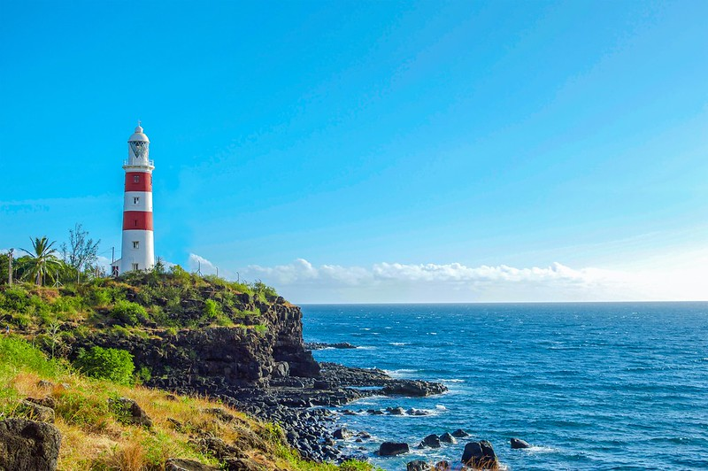 Red and white striped lighthouse on cliff, with bright blue sea to the left. It's a clear, sunny day and the sky is bright blue.