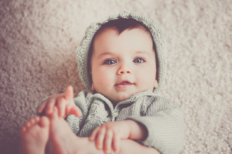 Baby boy with grey eyes wearing woolly hat and jumper, gazing up at parents.