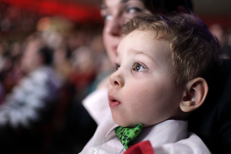 A little boy watching a musical with his parent.