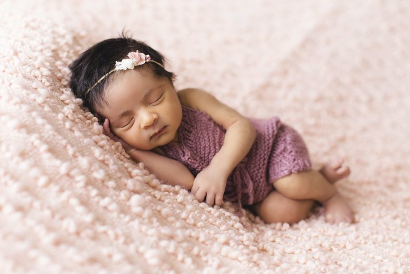 Baby girl wearing a flower hairband sleeping on a pink blanket.