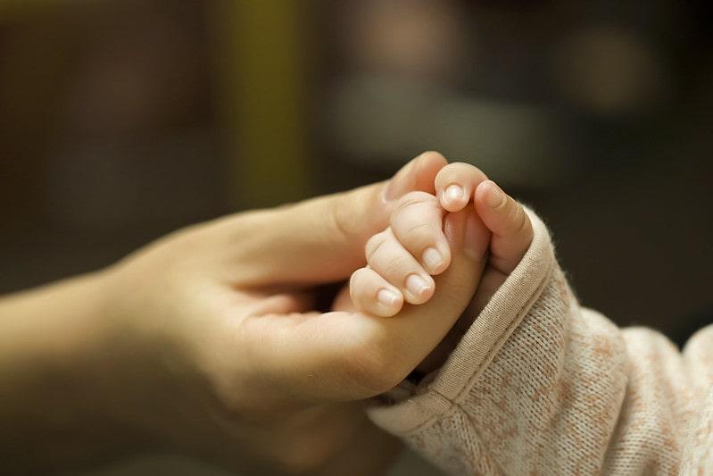 Mum holding hand of newborn baby girl.