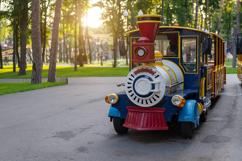 Colourful electric train in park.