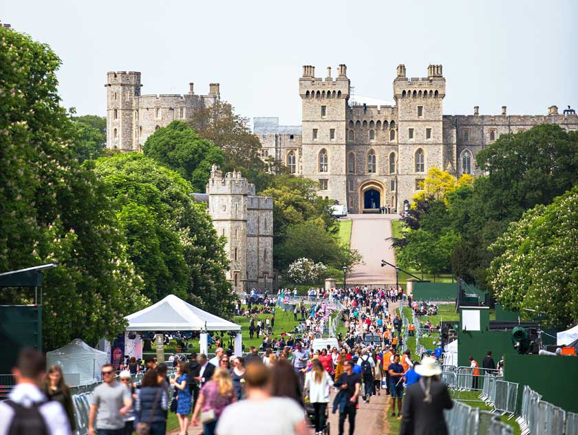 Windsor Castle from afar, with crowds lining the path to the entrance.