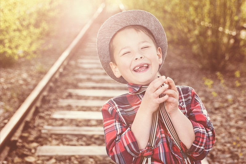 Boy laughing at a joke on a railway line.
