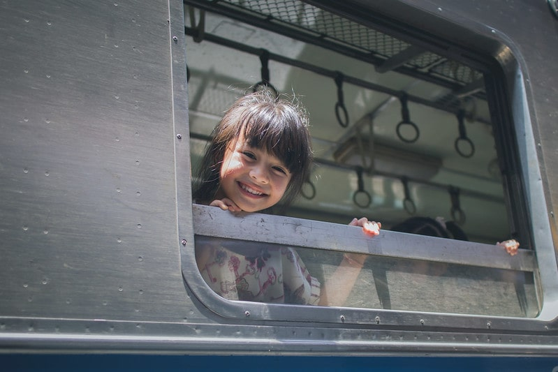 Girl smiling out the train window.