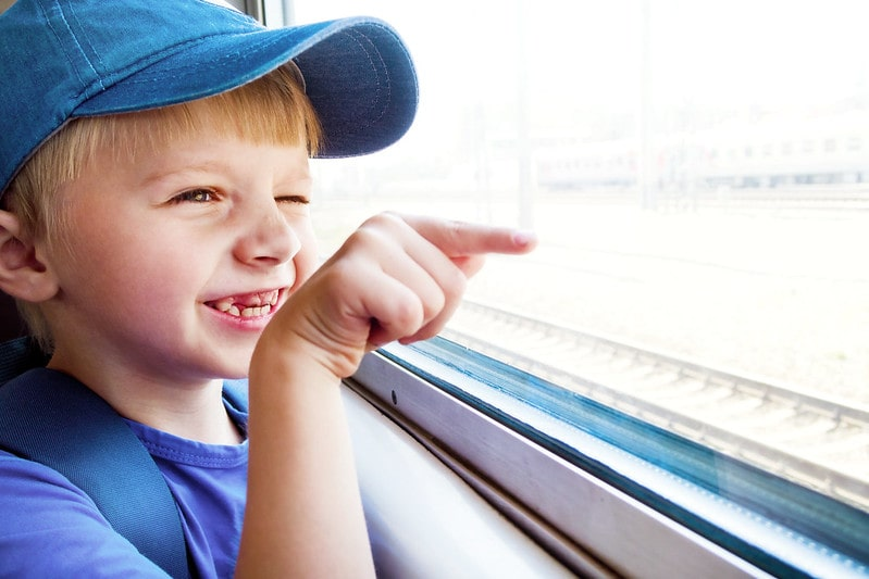 Boy looking out the train window smiling and pointing.