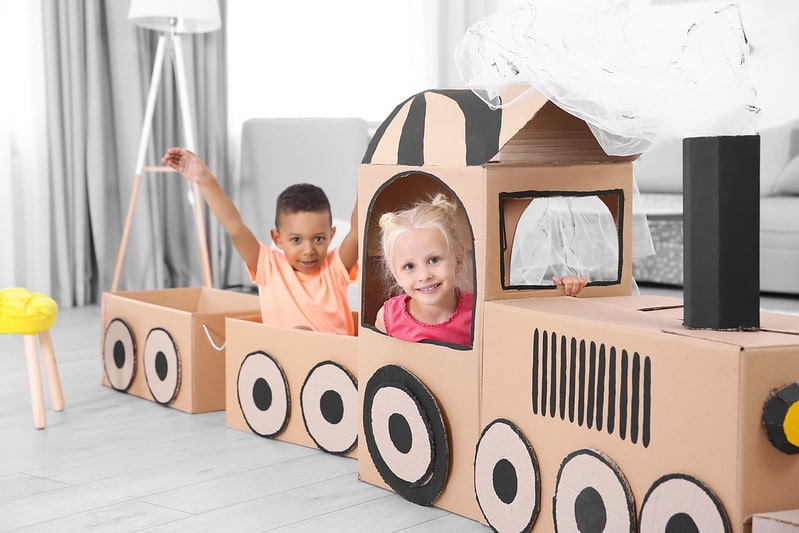 Children playing and smiling inside a cardboard train at home.
