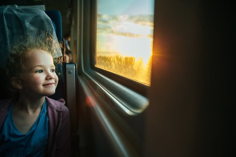 Girl smiling while looking out the train window.