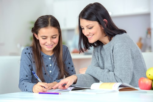 Mum and daughter smiling while learning spelling.