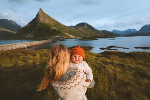 Mum holding baby in arms while looking out at the Norwegian landscape.
