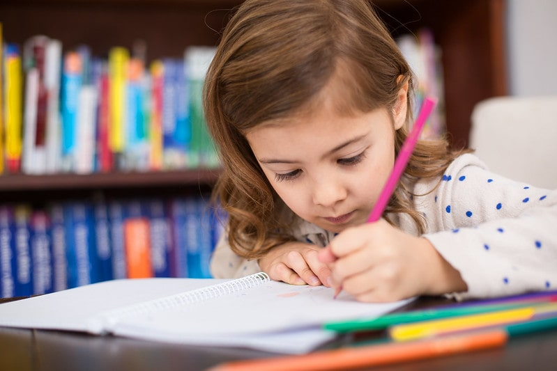 Little girl sitting at a desk writing in her exercise book with colouring pencils.