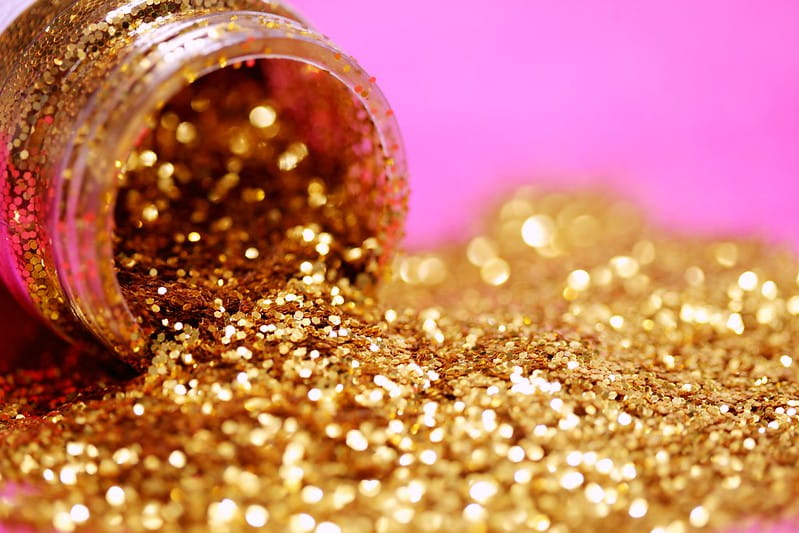 Pot of golden glitter spilling out on to a bright pink surface.