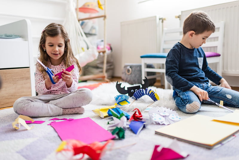 Two children sitting on the bedroom floor making paper crafts.