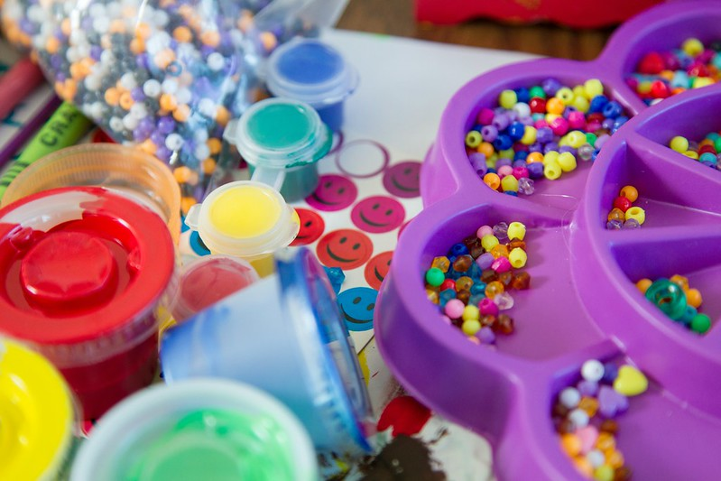 Assorted craft items such as rainbow paint, colourful beads and glitter.