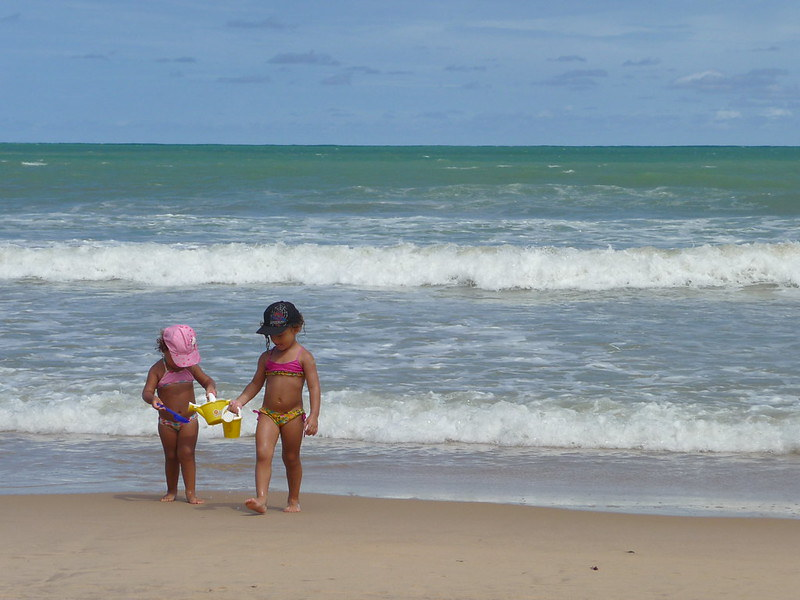 Two young children walking away from the sea up the sand carrying watering cans