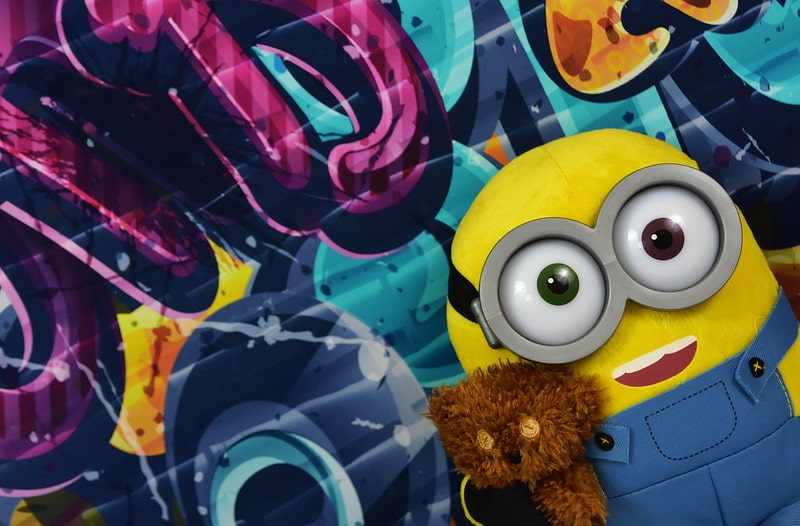 Minion standing in front of a graffiti wall holding a teddy bear.