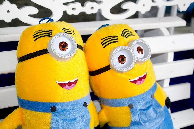 Two minion soft toys sat on a bench smiling into the distance.