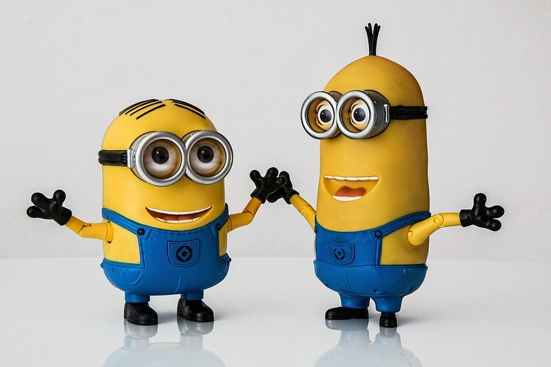 Two minions smiling with their arms outstretched.