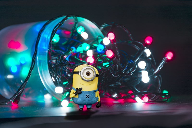 Minion standing in front of a jar with fairy lights spilling out of it.
