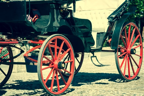 Side view of a Victorian carriage with big red wheels.