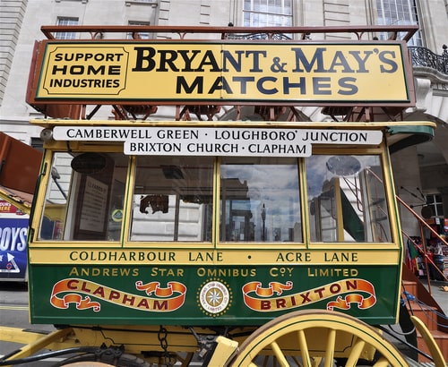 Victorian horse drawn bus with destinations written on side.
