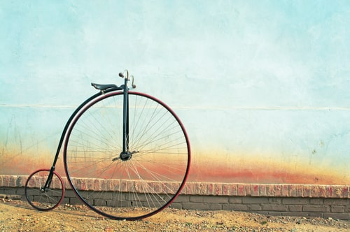 Penny farthing stationary next to a wall.