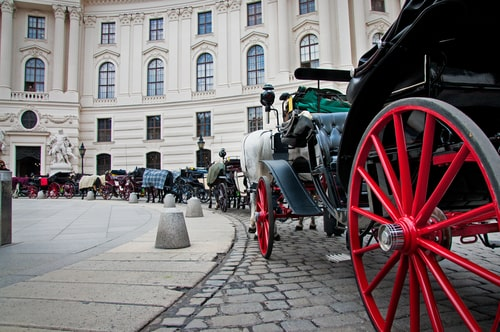 Victorian horse drawn stagecoaches in front of a grand building.