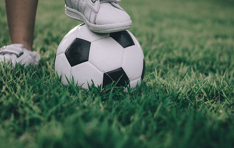 A child's foot on top of a football in the middle of a grassy field.