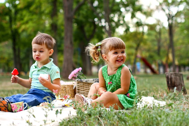 Little boy and girl sat on a rug on the grass outdoors enjoying a picnic.