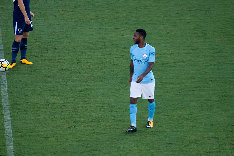 Footballer in blue clothes walking on the field in the middle of a game.