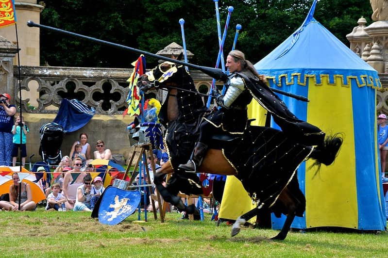 Man in Medieval attire on horseback jousting.
