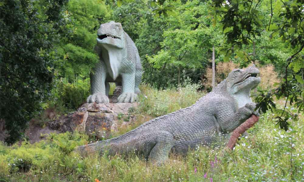 Dinosaur statues among the greenery in Crystal Palace Park.