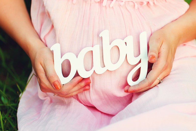 Mum-to-be wearing a pink dress holding the word baby over her bump.