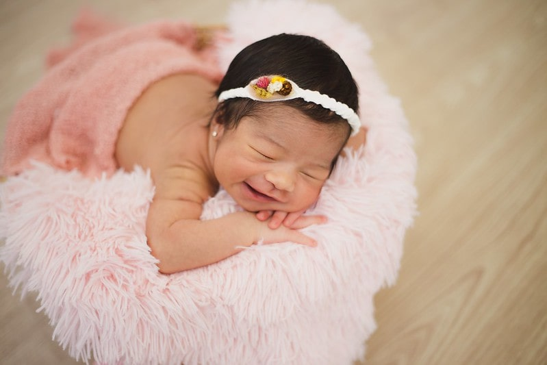 Baby girl wearing a knitted headband sleeping sweetly on a pink blanket.