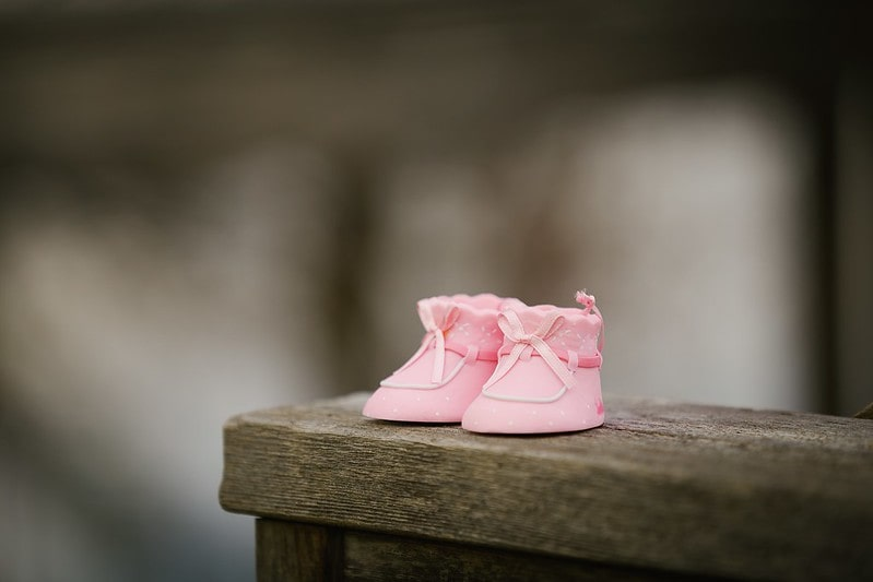 Little pink boots for a baby girl on a wooden wall.
