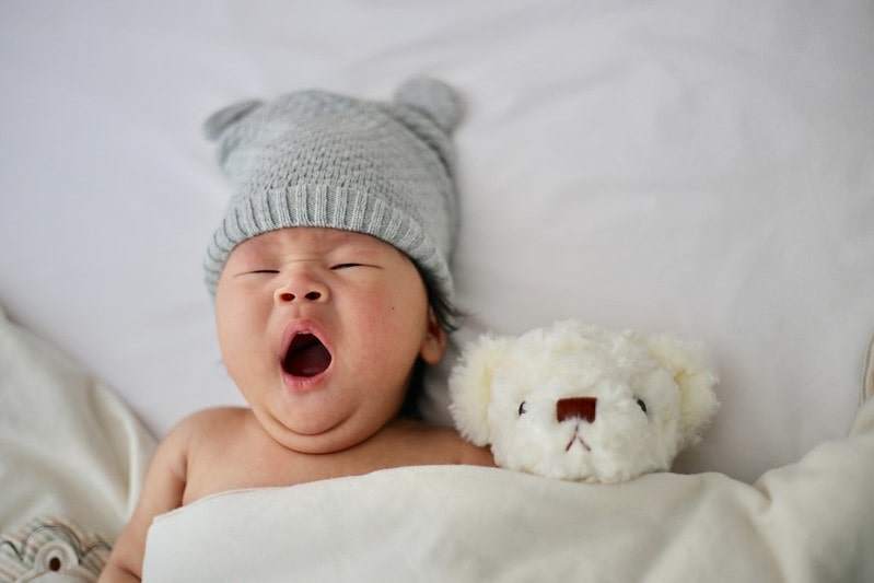 Baby wearing grey woolly hat lying in bed, yawning, next to a white teddy bear.