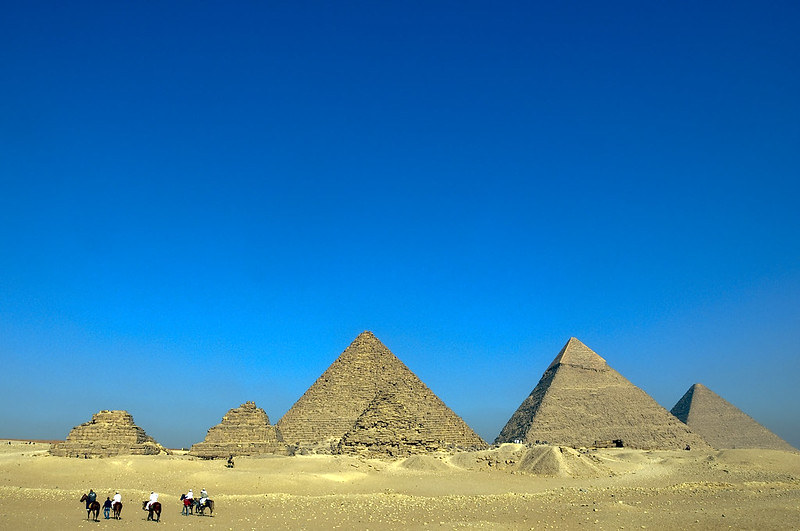 A desert with six pyramids in the centre, against a vivid blue sky on a sunny day.