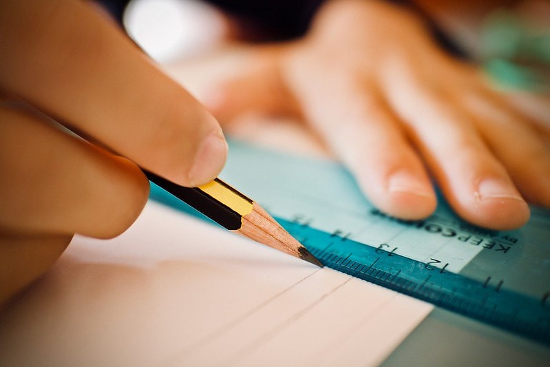 Close-up of someone trying to draw a straight line with a pencil and ruler. Their fingers, the pencil, the ruler, and the paper are in view.
