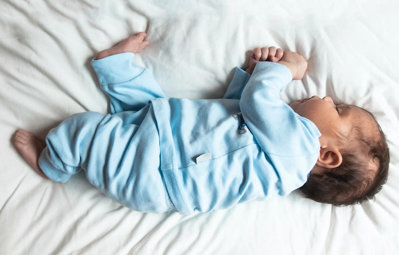 Baby boy wearing blue sweetly sleeping on the bed on his side.