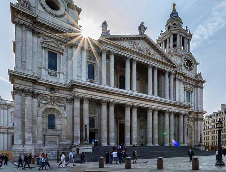 The exterior of St Paul's Cathedral in London against a blue sky.
