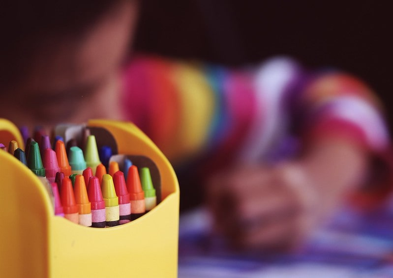 Crafts and Crayons With Girl in Background